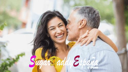 Hombre de mediana edad da un beso a su sugarbaby que sonrie